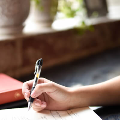 Photo close-up of a hand writing out a will by Hannah Olinger on Unsplash