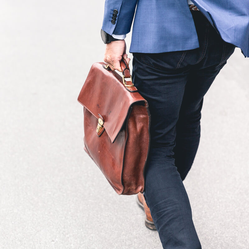Photo of left side of a man in a blue suit with leather briefcase walking away by Marten Bjork on Unsplash